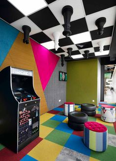 Google recreation room with upside down chess board on the ceiling, tyres ottoman to sit on, 8 bit arcade machine and full blown computer for consoles.