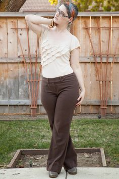 Cream ruffled tee, brown pinstriped slacks, and striped headscarf.