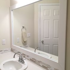 The frame around the mirror is done. I love the way it looks. It changed the entire look from a plain, boring builder grade mirror to a nice, custom framed mirror.  And all for around $40 #whiteliving #roommakeover #diybathroom #homeupdates #lowes #lightandbright #livingwithwhite #coastalstyle #bathroomdiy #bathroommakeover #mydiy #mosaictiles #glassmosaic #bathroomdesign #reloveyourroom @lindsay_hill_interiors by my_heatherwood