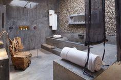 salle de bains minimaliste avec sol et murs en béton ciré, chaise design en bois fossilisé et parement mural en pierre naturelle