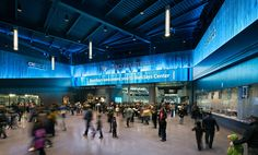 Dramatically lit Cascade Coil lends an intimate blue glow to the cavernous lobby of Barclays Center.  Architect: SHoP Architects Photography: Bruce Damonte Photography