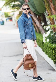 A jean jacket is worn with a little white dress, sneakers, and a leather bucket bag