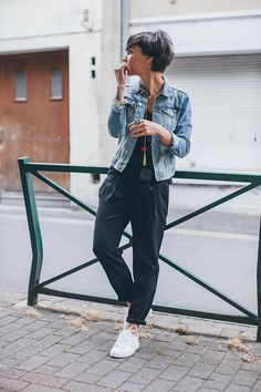 Denim jacket, black top, trousers + white trainers
