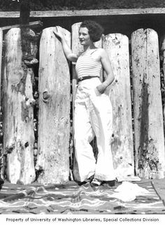 Wide legged white trousers with stripy top and narrow black belt, 1930s.