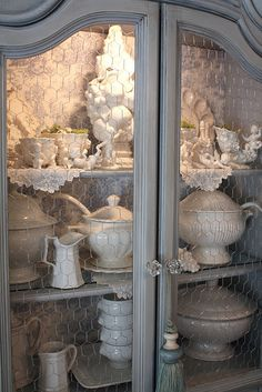 China cabinet painted blue, lined in toile paper, w/glass replaced by chicken wire. And, don't forget to hang a tassel!