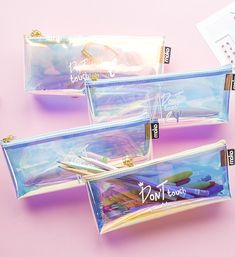 Shine bright like a diamond with this gorgeous 'Don't Touch Me' Holographic Pencil Case. It is made out of waterproof PVC which is transparent and holographic with tones of pink, violet and gold.