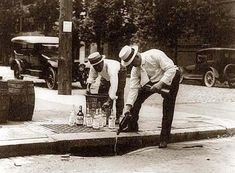 Pouring whiskey into a sewer during prohibition