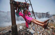 In Mumbai, der größten Stadt Indiens, spielt die fünfjährige Sana auf einer Müllhalde. Das Mädchen hat sich aus Kleiderfetzen an einem Signalpfosten der Eisenbahn eine Schaukel gebaut, im Hintergrund steigt Rauch von brennendem Müll auf.
