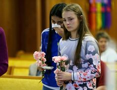 Rachel Marsh, 15, right, and Selena Orozco, 15, left, carry flowers as they attend a prayer service, Saturday, Sept. 24, 2016, at the Central United Methodist Church in Sedro-Woolley, Wash. The service was held in regard to Friday's fatal shooting of several people at a Macy's department store at the Cascade Mall in nearby Burlington, Wash. Both girls said they knew one of the victims of the shooting. (AP Photo/Ted S. Warren)