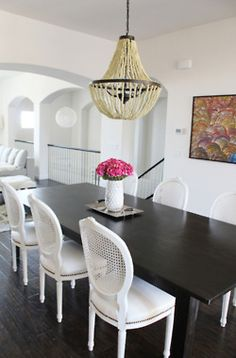 Dark floor and table with white chairs