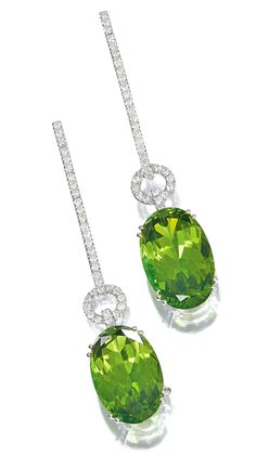 PAIR OF PERIDOT AND DIAMOND PENDENT EARRINGS.  Each oval peridot suspended from a line of  brilliant-cut diamonds, decorated with a similarly set annular motif, mounted in white gold.
