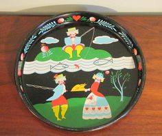 Black tray with a fishing theme to it.   This could be Dutch or Scandinavian.   It is trimmed with blue leaves and hearts.   The man is fishing and the
