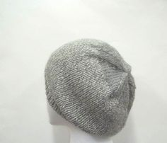 The colors in this hand knit beanie hat are medium gray and white. The look of a tweed with a gray crown. A warm comfy hat for winter days. Worn by men and women. This wool beanie beret is knitted with a soft pure wool yarn. See this hat at   http://www.CaboDesigns.etsy.com