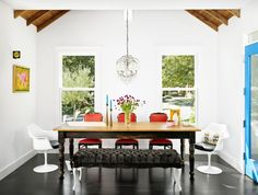 White molded plastic Eames chairs, vintage red chairs and black upholstered bench around rectantular wood dining table in Palma Residence in Austin Texas by Hugh Jefferson Randolph Architects, Photography by Casey Dunn | Remodelista