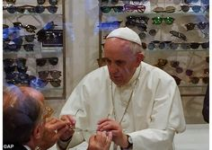 Pope Francis tries on a pair of spectacles in an eyeglass store in Via del Babuino in central Rome - AP