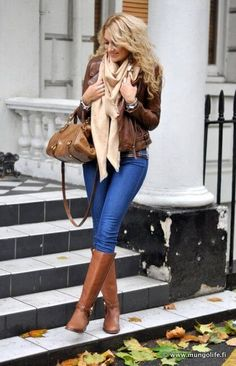 Woman wearing blue jeans, beige scarf, brown leather jacket and brown boots