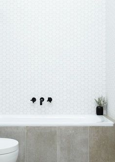 26 white large penny tiles over the bathtub - DigsDigs