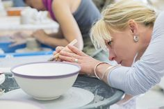 Woman decorating pottery