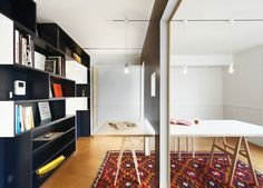 In this small, transformable apartment in Tokyo, Japan, ahole in the sliding wall fits over a ten-person diningtable, enabling it to be used in both the library and the meeting room. A movable wall clad in wainscoting on one side slides along tracks in the dining-room ceiling, dividing the room into a meeting space and a library.  Photo by: Ryohei Hamada
