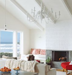 Living room in Arch Cape, Oregon with concrete-and-tile fireplace, vaulted, exposed-beam ceilings, a painted white chandelier, and neutral furniture