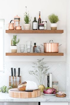 Kitchen counter with fresh bread and vegetables under wooden wall shelves