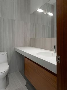 In this modern bathroom, large grey tiles, a white counter and wood vanity have been used to create a contemporary appearance. #ModernBathroom #GreyTiles #BathroomDesign