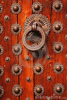 Closeup of old wooden door with ironwork design and knocker. By Serban Enache.