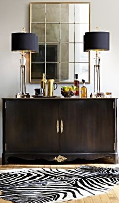 An ebony homage to regency style, this stunning bar cabinet is designed to look like a fine buffet or sideboard.