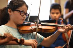 """Sixth-grader Jayda Bernadac, 11, rehearses notes using a violin during a string orchestra class Sept. 3 at Horizon Middle School in District 49. """"At first, I had trouble with it, but once you really get it, it's easy,"""" said Jayda, who started playing in fifth grade. """"I didn't see it in my future to be a professional violinist, but now I do. If I keep playing, I'll get really good."""" Her teacher, Catherine Camp-Davidson, received a gift of 10 violins during a presentation Aug. 29 in Denver."""