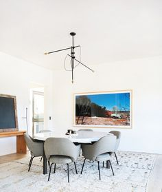 Modern dining space with light fixture, oversized artwork, and round table