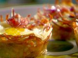 "Eggs in Baskets - hashbrown ""baskets"" with eggs topped with bacon & cheese made in muffin pan..."