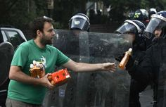 LONDON, ENGLAND - AUGUST 08: A Hackney resident hands out fizzy drinks to riot police after disturbances in Hackney have died down on August 8, 2011 in London, England. Pockets of rioting and looting continues to take place in various parts of London this evening prompted by the initial rioting in Tottenham and then in Brixton on Sunday night. Disturbances broke out late on Saturday night in Tottenham and the surrounding area after the killing of Mark Duggan, 29 and a father-of-four, by…