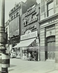 'Chocolate King' sweetshop, Upper Street, Islington, London, 1944. Man, woman and child standing in front of a sweet shop and tobacconist's advertising Palm toffee. In the foreground is a litter bin attached to a lamppost, with an outfitter's beyond.