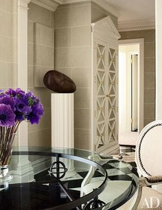A pedimented cabinet conceals a structural column in the entryway, which is lined in a faux-stone wallpaper.