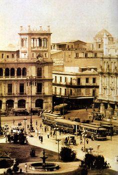 Esquina suroeste del Zocalo, a la izquierda el Palacio del Ayuntamiento ya remodelado y a la derecha el Centro Mercantil que dio paso al Gran Hotel de la Ciudad de Mexico. Se aprecian los tranvias, asi como un zocalo con jardineras y fuentes. Al fondo se observa la cupula delTemplo de San Agustin. El edificio al centro entre las calles de 16 de Septiembre antes Tlapaleros y Monterilla (5 de febrero) existe actualmente. Imagen de 1925
