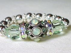 STRETCH RING F1: SWAROVSKI GREEN ENCRUSTED FILIGREE , AB RONDELLES ON A 925 STERLING SILVER BAND MADE OF DAIST'S AND ROUNDS...