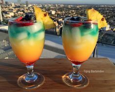 RAINBOW BREEZE Red Layer: 1 /2 oz. (15ml) Grenadine Fill Glass with Ice  Yellow Layer: 1 oz. (30ml) Pineapple Rum 1 oz. (30ml) Banana Rum 1 oz. (30ml) Pineapple Juice 1 oz. (30ml) Orange Juice  Blue Layer: 1 oz. (30ml) Pineapple Vodka 1/2 oz. (30ml) Blue Curacao  Blueberries Strawberry Slices Orange Slices Pineapple Slices