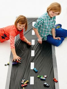 Fold a 54- by 108-inch black vinyl tablecloth in half lengthwise to create a strip 27 inches wide. Line the edges with checkerboard duct tape and add white duct tape lane markings. Adhere the cloth to the floor with a low-tack tape,  such as painter's tape, then let kids race -- or, more likely, crash! -- their cars. Note:  Tape may damage the finish on certain hardwoods, so set up the track on concrete or linoleum, if possible.                 Originally published in the March 2014 issue…