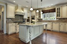 Ornate white kitchen cabinets throughout this custom kitchen with ornate matching island with dark wood flooring throughout