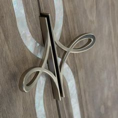 Straight Up with a Twist. Each door is banded in white Mother of Pearl and custom designed door pulls, both featuring a scroll motif that is carried through to the metal stretcher uniting its slim legs.