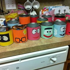 DIY Yo Gabba Gabba Party Favor Tins/Decoration.  Save formula tins or some other tin container you buy a lot. Then wrap with construction paper. Use construction paper and black marker to make faces and glue on to tins! Use as table centerpieces vases or to fill up with goodies! #birthday #party #yo #gabba #gabba #yogabbagabba #nick #junior #jr #nickjr #nickelodeon #children #toddler #diy #craft #project #gift #favor #goddiebag #Goodies #tin