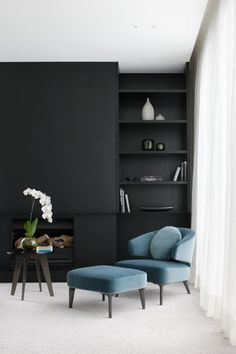 The startling matte black walls and stark white drapes of this #modern living room make the bright teal chair and ottoman pop even more!