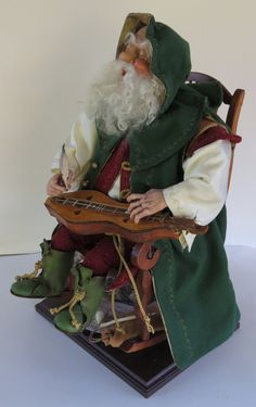 Santa sings a soulful rendition of an old English Christmas Carol, The Holly And The Ivy, while accompanying himself on a Mountain Dulcimer. This Santa is a Handcrafted Santa Doll by artist Walt Carter. Each Santa is entirely handmade using various high quality materials. Walt hand sculpts each Santas face and hands without the use of molds or forms. Additionally, each Santas costume is individually designed, hand sewn and embellished.  Items Used: Polymer Clay, Wood for Dulcimer, Vintage…