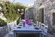 Greek café chairs surround a table on the dining terrace; dry stone walls sheath the exterior of the house.