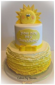 I love the sun! If we could have a sun on top of a blue top tier, with a white cloud & gray script and the bottom tier the gray & white chevron. Optional yellow bow...