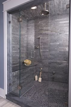 Dark grey wall tiles can create a designer look on a budget! This stunning shower enclosure is the ultimate choice in luxury and features an over head rain-effect shower too!