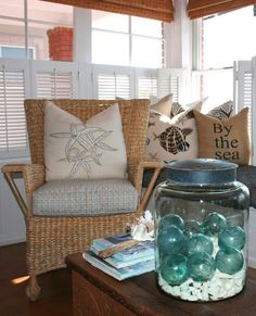 antique glass fishing floats on top of white shells in apothecary jar w/ tin lid ....Idea to note: add old b/w photo inside of beach vacations