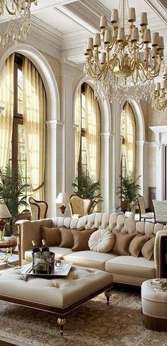 Large windows flank this gorgeous beige living room with chandelier | traditional living room | home decor