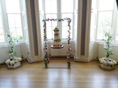 Cake Swing for your faux wedding cakes.  Flower-covered rose cake swing and wooden slice for beautiful wedding cake pictures without the cost.  We can supply the swing, cakes, flower decorations, as well as deliver, set-up and collect the day after your wedding for a fraction of the cost of a 3 tier wedding cake. More details at www.limelightweddings.co.uk Manzanita Tree Centerpieces, Flower Decorations, Wedding Decorations, 3 Tier Wedding Cakes, Led Tree, Wooden Slices, Wedding Place Settings, Wedding Hire, Rose Cake