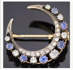 Diamonds and sapphires on crescent moon brooch